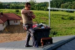 W słoneczny letni dzień praca instalatora RTV na dachu